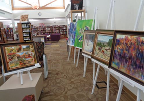 Paintings displayed on easels in the library